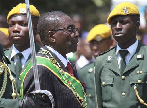 "In this file photo taken Tuesday, Sept. 17, 2013 Zimbabwean President Robert Mugabe inspects the guard of honor during the opening of the first session of the eighth Parliament of Zimbabwe in Harare.  Zimbabwe's longtime President Robert Mugabe says he doesn't want anyone to be fooled by his impeccable Western style of dress and his precise, teacherly use of English: He is African through and through. ""I am not British, I am not a colonial product because I am a complete Zimbabwean, "" he told graduates at Great Zimbabwe University near the remains of the 13th Century walled city, for which Zimbabwe, the former colony of Rhodesia, is named. (AP Photo/Tsvangirayi Mukwazhi-file)"