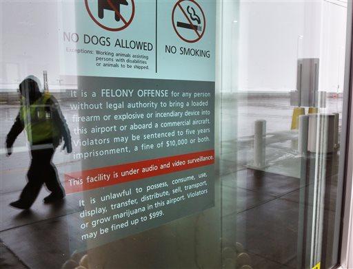 A security officer walks near a notice prohibiting marijuana possession at Denver International Airport, Monday, Jan. 27, 2014. (AP Photo/Brennan Linsley)
