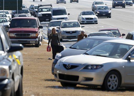 Karen Hurst, left, carries a gas can as she helps Ann Batsun, recover her car on Interstate 75  Thursday, Jan. 30, 2014, in Atlanta. (AP Photo/John Bazemore)