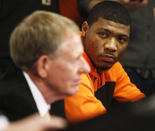 Oklahoma State basketball player Marcus Smart, right, and OSU athletic director Mike Holder look on during during a news conference in Stillwater, Okla., Sunday, Feb. 9, 2014, in regard to Smart shoving a fan during an NCAA college basketball game the day before. (AP Photo/The Oklahoman, KT King)