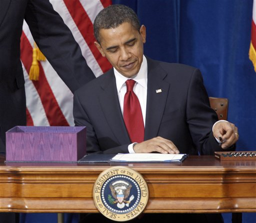 This Feb. 17, 2009 file photo shows President Barack Obama picking up the first pen to sign the economic stimulus bill during a ceremony in the Museum of Nature and Science in Denver. (AP Photo/David Zalubowski, File)
