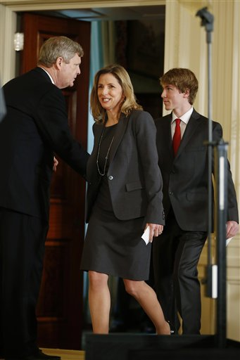 Agriculture Secretary Tom Vilsack, left, introduces JoAnne Hammermaster, from Vienna, Va., who is co-founder and president of Real Food For Kids, and her son Sam Hammermaster, before first lady Michelle Obama announced proposed guidelines for local school wellness policies during an event in the East Room at the White House in Washington, Tuesday, Feb. 25, 2014. (AP Photo/Charles Dharapak)