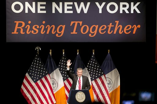 New York Mayor Bill de Blasio waves to the audience a he walks to the podium to deliver the State of the City address at LaGuardia Community College in the Queens borough of New York, Monday, Feb. 10, 2014. (AP Photo/Mark Lennihan)