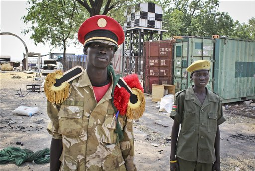 In this photo taken Wednesday, Feb. 26, 2014, rebels proclaiming to be part of the Nuer tribe's infamous 'White Army' stand in the grounds of the hospital in Malakal, South Sudan. (AP Photo/Ilya Gridneff)
