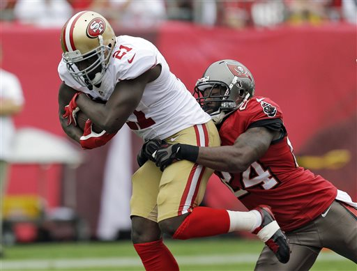 FILE - In this Dec. 15, 2013, file photo, San Francisco 49ers running back Frank Gore (21) is grabbed by Tampa Bay Buccaneers cornerback Darrelle Revis (24) during the first quarter of an NFL football game in Tampa, Fla. (AP Photo/Chris O'Meara, File)