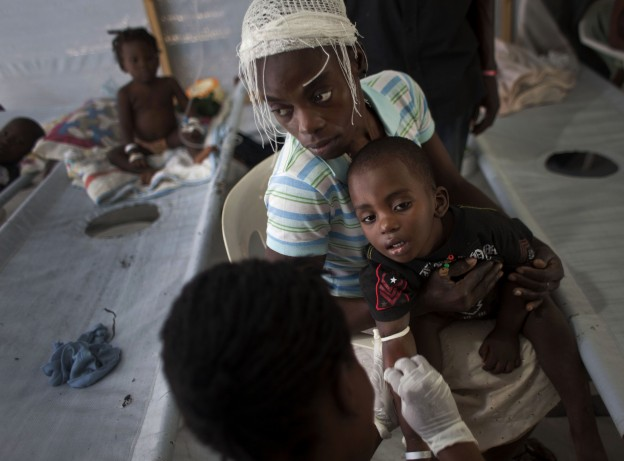 A woman holds her sick child as he receives treatment for cholera at a Doctors Without Borders, MSF, cholera clinic in Port-au-Prince, Haiti. (AP)