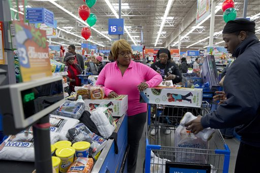 In this Wednesday, Dec. 4, 2013, file photo, April Taylor of Upper Marlboro, Md., left, buys items from groceries to Christmas presents with her son Jarhon Taylor, right, on opening day of a new Wal-Mart on Georgia Avenue in Northwest Washington. (AP Photo/Jacquelyn Martin, File)