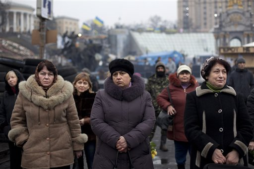 People attend a funeral ceremony for Andryi Pozniak, 25, a self defense volunteer who was shot and killed by an unknown assailant two days ago near Kiev's Independence Square, Ukraine, Thursday, March 6, 2014. (AP Photo/David Azia)