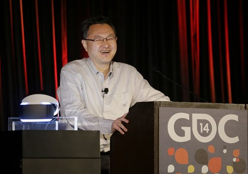 Shuhei Yoshida, president of Sony Computer Entertainment Worldwide Studios, speaks after unveiling the PlayStation 4 virtual reality headset Project Morpheus, pictured at left, at the Game Developers Conference 2014 in San Francisco, Tuesday, March 18, 2014.  (AP Photo/Jeff Chiu)