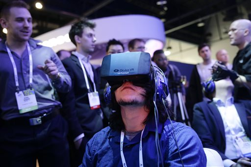 In this Jan. 7, 2014 file photo, show attendees play a video game wearing  Oculus Rift virtual reality headsets at the Intel booth at the International Consumer Electronics Show(CES), in Las Vegas. Facebook said Tuesday, March 25, 2014,  it has agreed to buy Oculus for $2 billion, betting that its virtual reality may be a new way for people to communicate, learn or be entertained. (AP Photo/Jae C. Hong, File)