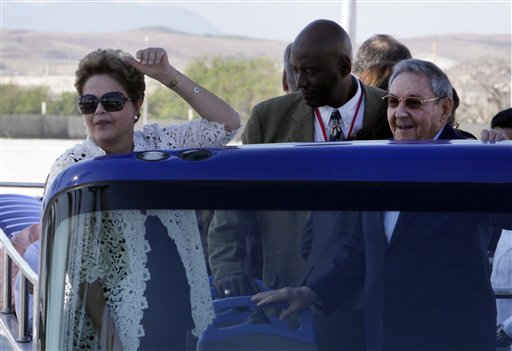 In this Jan. 27, 2014, file photo, Brazil's President Dilma Rousseff, left, and Cuba's President Raul Castro make a tour by bus after the inauguration ceremony of the first phase of a port overhaul project in Mariel, Cuba. Cuban authorities are on the verge of enacting a new foreign investment law considered one of the most vital building blocks of President Raul Castro's effort to reform the country's struggling economy. Foreign investment in the Communist-run country has lagged behind expectations in recent years, and the shortfall is seen as a major reason for disappointing economic growth. (AP Photo/Ismael Francisco, Cubadebate, File)
