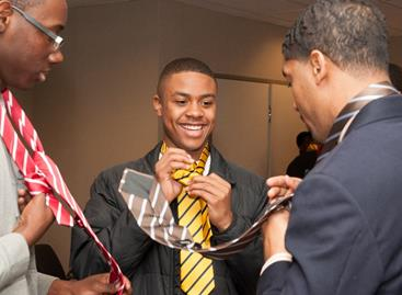 """Fonzworth Bentley teaches students the proper way to tie a Windsor knot at the """"Tied to Greatness"""" workshop during the UNCF Empower Me Tour presented by Wells Fargo in Charlotte, NC."""