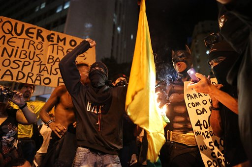 Masked demonstrators set fire to a jersey with the colors of Brazilian national soccer team during protest against the World Cup 2014, in Rio de Janeiro, Brazil, Thursday, March 27, 2014. Demonstrators call for better schools, health care, questioning the billions spent to host this year's World Cup and the 2016 Olympics. (AP Photo/Leo Correa)