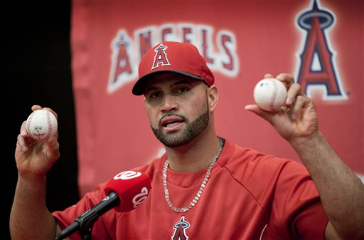 Los Angeles Angels Albert Pujols holds up the balls that he hit for his 499th, right, and 500th, left, career homers during a new conference following a baseball game against the Washington Nationals, Tuesday, April 22, 2014 in Washington. The Angels won the game 7-2. (AP Photo/Pablo Martinez Monsivais)