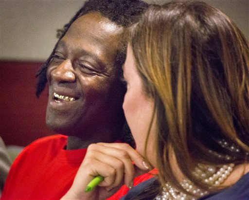 Rapper Flavor Fav, left, laughs his attorney Kristina Wildveld in Clark County District Court on Monday, April 14, 2014, in Las Vegas. Flavor Flav has pleaded guilty to reduced charges in a Las Vegas domestic violence case in a move that will avoid a trial and possible jail time. He acknowledged Monday in court that he wielded a kitchen knife during an October 2012 argument at home with his longtime girlfriend's 17-year-old son. (AP Photo/Las Vegas Review-Journal, Jeff Scheid)