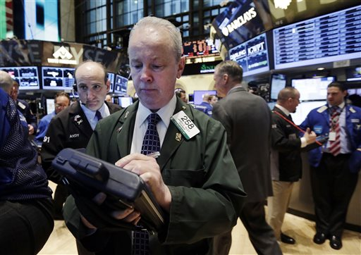Trader James Riley, center, works on the floor of the New York Stock Exchange, Tuesday, April 8, 2014. Stocks were mixed in early trading on Tuesday after a three-day slump. Investors will start to focus on company earnings this week. (AP Photo/Richard Drew)