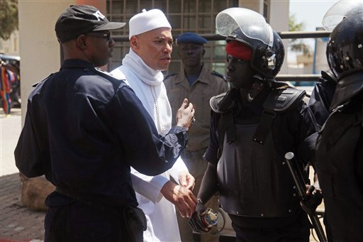 In this Friday, March 15, 2013 file photo, Karim Wade, center, the son of former Senegalese President Abdoulaye Wade, is blocked by police as he tries to approach journalists and gathered supporters outside the office of the special prosecutor investigating him on charges of embezzled funds, in Dakar, Senegal. (AP Photo/File)
