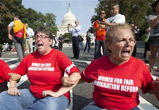 This Sept. 12, 2013 file photo shows women linking their arms and sit in a circle to block the intersection of Independence Avenue SE and New Jersey Avenue SE outside the House of Representatives on Capitol Hill in Washington to protest Congress' inaction on comprehensive and inclusive immigration reform. (AP Photo/Carolyn Kaster, File)