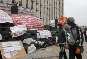 Masked pro-Russian activists pass by a barricade as they guard a regional administration building that they had seized earlier in Donetsk, Ukraine, Friday, April 11, 2014. (AP Photo/Efrem Lukatsky)