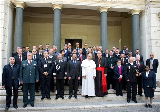 In this photo released by Vatican newspaper L'Osservatore Romano Pope Francis poses for a photo with participants in a conference about the human trafficking,  at the Vatican, Thursday, April 10, 2014. Pope Francis has denounced human trafficking as a crime against humanity after meeting with four women who were forced into prostitution.  Francis attended a Vatican conference Thursday of church workers, charity representatives and police chiefs from 20 nations, who pledged greater cooperation to encourage victims of trafficking and slavery to come forward.  (AP Photo/L'Osservatore Romano)