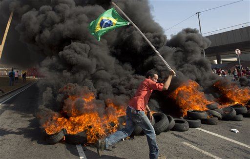 A member of the Homeless Workers Movement carries a Brazilian flag past burning tires during a protest against the money spent on the World Cup near Itaquerao stadium which will host the international soccer tournament's first match in Sao Paulo, Brazil, Thursday, May 15, 2014. Brazilians are angry at the billions spent to host the World Cup, much of it on 12 ornate football stadiums, one-third of which critics say will see little use after the big event. (AP Photo/Andre Penner)