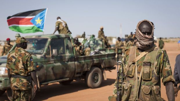 A South Sudanese government soldier stands with others near their vehicles, after government forces on Friday retook from rebel forces the provincial capital of Bentiu, in Unity State, South Sudan, Sunday, Jan 12, 2014. (AP Photo/Mackenzie Knowles-Coursin)