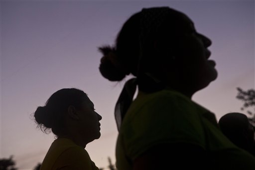 """In this Saturday, July 19, 2014 photo, Elsa Ramirez, 27, left, deported from the United States with her children a day earlier, prays at a local outdoor church youth meeting for youth, in Tocoa, Honduras. With her husband's killers still on the loose, Ramirez says she may try again to make the trek to the United States--the next time without her children. """"I wish I could divide myself in two,"""" Ramirez said. """"I want to be here and there, there to give my children a better future, """"she said. (AP Photo/Esteban Felix)"""