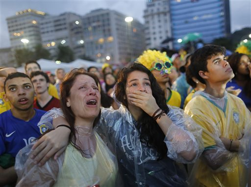 Brazil soccer fans cry as they watch their team play a World Cup semifinal match against Germany on a live telecast inside the FIFA Fan Fest area on Copacabana beach in Rio de Janeiro, Brazil, Tuesday, July 8, 2014. (AP Photo/Leo Correa)