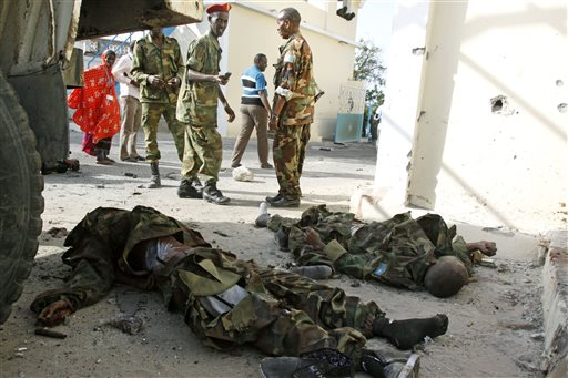 GRAPHIC CONTENT - Somali government soldiers look at the dead bodies of al-Shabab militants on a road near the main gate of the presidential palace in Mogadishu, Somalia, Wednesday, July, 9, 2014. Somali troops retook the presidential palace in the capital of Mogadishu after militants forced their way in and exchanged heavy gunfire with troops and guards Tuesday, the latest attack underscoring the threat posed by Islamic extremist group al-Shabab in east Africa.  (AP Photo/Farah Abdi Warsameh)