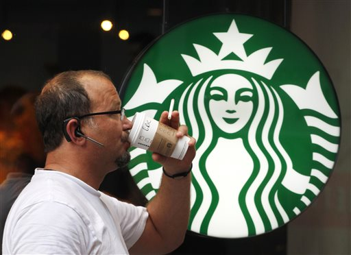 In this July 11, 2013  file photo, a man drinks a Starbucks coffee in New York. Starbucks reports quarterly financial results on Thursday, July 24, 2014. (AP Photo/Mark Lennihan, File)
