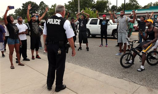 Protestors blocking Florissant Road raise their hands after being approached by police officers who asked them to stop blocking the street in front of the Ferguson police department on Sunday, Aug. 10, 2014, one day after a Ferguson officer shot and killed Michael Brown. Officers backed down and instead barricaded the street in both directions. (AP Photo/St. Louis Post-Dispatch, Robert Cohen)