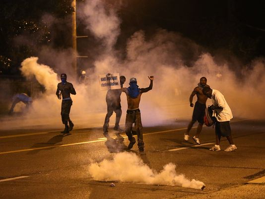 People protest as tear gas canisters detonate around them on Wednesday, in Ferguson, Mo. (AP/Chris Lee, St. Louis Post-Dispatch)