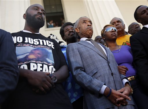 Civil rights leader Rev. Al Sharpton, center, stands with the parents of Michael Brown, Lesley McSpadden, right, and Michael Brown Sr., left, during a news conference outside the Old Courthouse Tuesday, Aug. 12, 2014, in St. Louis. Brown Jr., 18, who was unarmed, was shot to death Saturday by a Ferguson police officer while walking with a friend down the center of the street. (AP Photo/Jeff Roberson)