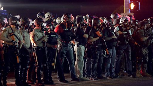 Police in riot gear mobilize during a standoff with protesters Monday, Aug. 18, 2014, during a rally for Michael Brown, who was killed by a police officer Aug. 9 in Ferguson, Mo. Brown's shooting has sparked more than a week of protests, riots and looting in the St. Louis suburb. (AP Photo/Charlie Riedel)