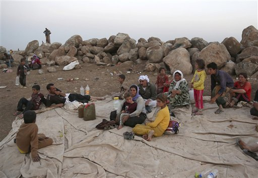 Displaced Iraqis from the Yazidi community settle at a camp in Derike, Syria, Sunday, Aug. 10, 2014. Kurdish authorities at the border believe some 45,000 Yazidis passed the river crossing in the past week and  thousands more are still stranded in the mountains. (AP Photo/ Khalid Mohammed)
