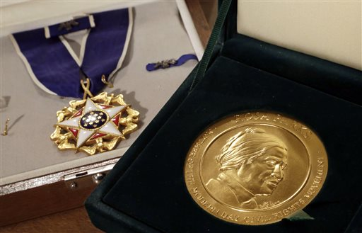 In this March 14, 2014, file photo, Rosa Parks' Presidential Medal of Freedom, left, and her Congressional Gold Medal are displayed at Guernsey's auction house, in New York. Hundreds of items that belonged to civil rights icon Rosa Parks that have been sitting unseen for years in a New York warehouse have been sold to a foundation run by the son of billionaire investment guru Warren Buffett, the younger Buffett said Thursday, Aug. 28. Howard G. Buffett told The Associated Press that his foundation plans to give the items, which include Parks' Presidential Medal of Freedom, to an institute he hasn't yet selected. (AP Photo/Richard Drew, File)