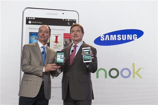 Tim Baxter, president of Samsung Electronics America, left, and Mike Huseby, CEO of Barnes & Noble, pose for a photograph during the unveiling of the Samsung Galaxy Tab 4 Nook, a co-branded tablet that will replace B&N's Nook, Wednesday, Aug. 20, 2014, in New York. The 7-inch tablet will sell for $179 after a $20 instant rebate, the same entry price of the non-branded Samsung Galaxy Tab 4. (AP Photo/John Minchillo)