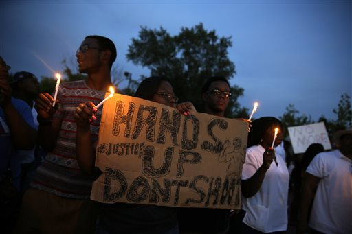 Demonstrators hold candles and signs Thursday, Aug. 14, 2014, in Ferguson, Mo. Hundreds of people protesting the death of  Michael Brown marched through the streets of Ferguson alongside state troopers Thursday. (AP Photo/Jeff Roberson)