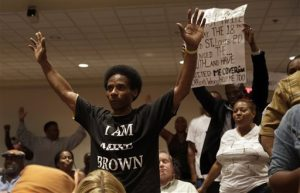 Larry Miller holds up his hands after speaking during a public comments portion of a meeting of the Ferguson City Council Tuesday, Sept. 9, 2014, in Ferguson, Mo. The meeting is the first for the city council since the fatal shooting of Michael Brown by a city police officer. (AP Photo/Jeff Roberson)