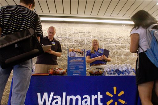 In this Thursday, Sept. 1, 2011, photo, Wal-Mart employees Jon Christians and Lori Harris take job applications and answers questions during a job fair at the University of Illinois Springfield campus in Springfield, Ill. Wal-Mart Stores Inc. says it plans to hire 60,000 temporary holiday workers for the crucial holiday season in 2014, an increase of nearly 10 percent from last year. (AP Photo/Seth Perlman, File)