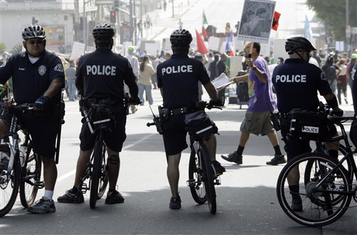 In this Sept. 18, 2010 file photo, officers on bicycles keep watch as demonstrators protesting several incidents of alleged Los Angeles Police Department brutality, including the fatal shooting of Manuel Jamines a month ago, stand outside the LAPD's Rampart Station in the Westlake district of Los Angeles. Police departments across the U.S. are using technology to try to identify problem officers before their misbehavior harms innocent people, embarrasses their employer, or invites a costly lawsuit,  from citizens or the federal government.  The Los Angeles Police Department agreed to set up their $33 million early warning systems after the so-called Rampart scandal in which an elite anti-gang unit was found to have beaten and framed suspected gang members. The system was then implemented in 2007. (AP Photo/Reed Saxon)