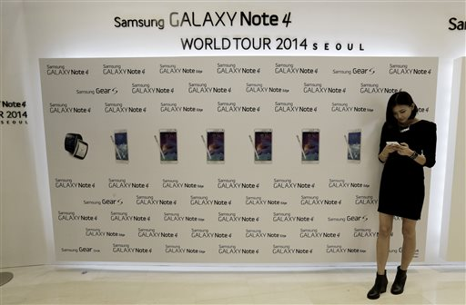 A model tries out a Samsung Electronics Co.'s latest Galaxy Note 4 smartphone as it is unveiled in Seoul, South Korea, Wednesday, Sept. 24, 2014. Samsung said Wednesday its latest Galaxy Note 4 smartphone will go on sale in China and South Korea later this week as its flagging mobile business tries to defend sales from Apple's new iPhones. Samsung said all three Chinese mobile carriers and all three South Korean mobile operators will begin Galaxy Note 4 sales on Friday. (AP Photo/Ahn Young-joon)