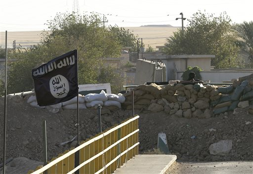 A black flag used by the Islamic State group flutters over their combat positions on the front line with Kurdish Peshmerga fighters at the Mullah Abdullah Bridge, located between Irbil and Kirkuk, 290 kilometers (180 miles) north of Baghdad, Iraq, Saturday, Sept. 27, 2014. (AP Photo/Hadi Mizban)