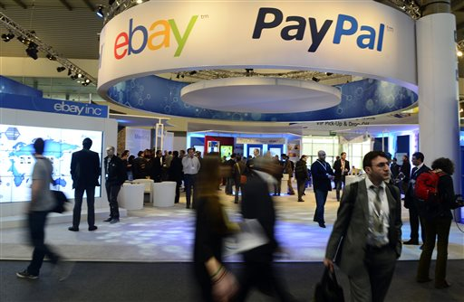 In this Wednesday, Feb. 27, 2013, file photo, attendees walk in front of an EBay and PayPal display area at the Mobile World Congress, the world's largest mobile phone trade show, in Barcelona, Spain. PayPal is splitting from EBay Inc. and will become a separate and publicly traded company during the second half of 2015. (AP Photo/Manu Fernandez, File)