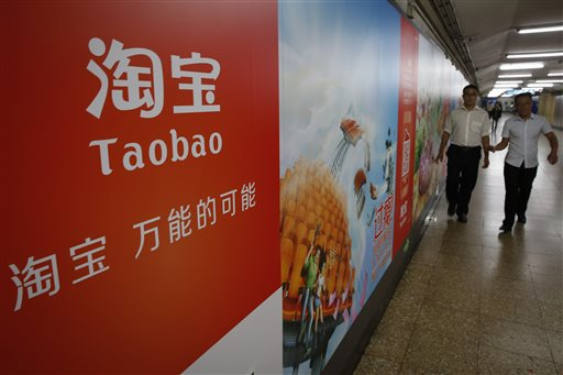 People walk past an advertising billboard showing the mobile app of Alibaba's Taobao consumer-to-consumer site at a subway station in Beijing Thursday, Sept. 18, 2014. Alibaba Group's U.S. stock offering is a wakeup call about an emerging wave of technology giants in China's state-dominated economy. (AP Photo/Vincent Thian)