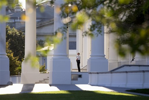 In this Sept. 22, 2014 file photo, a member of the Secret Service Uniformed Division looks out from the North Portico of the White House in Washington. Secret Service Director Julia Pierson said Tuesday the front door to the White House now locks automatically in a security breach. Pierson told a House panel that the switch to automatic locks at the White House's north door was made after an Army veteran jumped the fence on Sept. 19 and made his way into the interior of the building through two unlocked doors. (AP Photo/Carolyn Kaster, File)