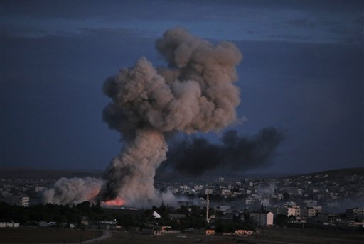 Thick smoke from an airstrike by the US-led coalition rises in Kobani, Syria, during fighting between Syrian Kurds and the militants of Islamic State group, as seen from a hilltop on the outskirts of Suruc, at the Turkey-Syria border, Monday, Oct. 20, 2014. Kobani, also known as Ayn Arab, and its surrounding areas, has been under assault by extremists of the Islamic State group since mid-September and is being defended by Kurdish fighters. (AP Photo/Lefteris Pitarakis)