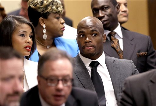 Minnesota Vikings running back Adrian Peterson, right, sits with his wife Ashley Brown Peterson, left, during his first court appearance Wednesday, Oct. 8, 2014, in Conroe, Texas A Texas judge has tentatively set a Dec. 1 trial date for Peterson on a charge of felony child abuse for using a wooden switch to discipline his 4-year-old son. (AP Photo/David J. Phillip, Pool)