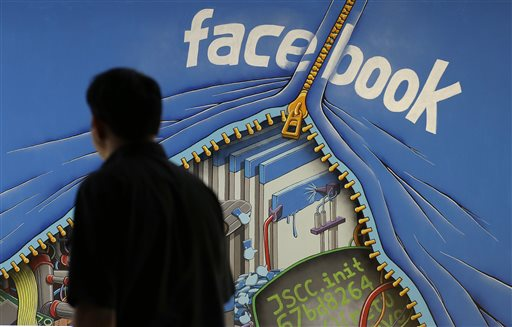 In this June 11, 2014 photo, a man walks past a mural in an office on the Facebook campus in Menlo Park, Calif. Facebook reports quarterly earnings on Tuesday, Oct. 28, 2014. (AP Photo/Jeff Chiu)