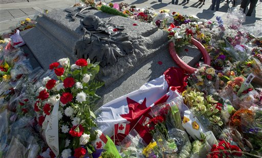 Flowers and flags over a memorial at the Tomb of the Unknown Soldier is pictured at the National War Memorial, in Ottawa on Friday, Oct. 24, 2014.  Canadians are mourning the loss of Cpl. Nathan Cirillo, the army reservist who was shot dead as he stood guard before the Tomb of the Unknown soldier on Wednesday.  (AP Photo/The Canadian Press, Justin Tang)